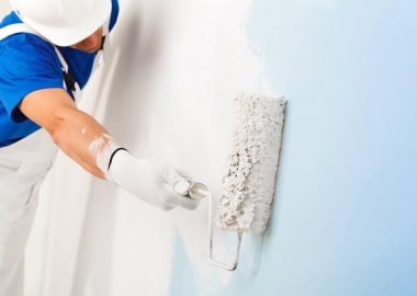 side view of  painter in white dungarees, helmet and gloves painting a wall with paint roller,  with copy space, selective focus on paint roller
